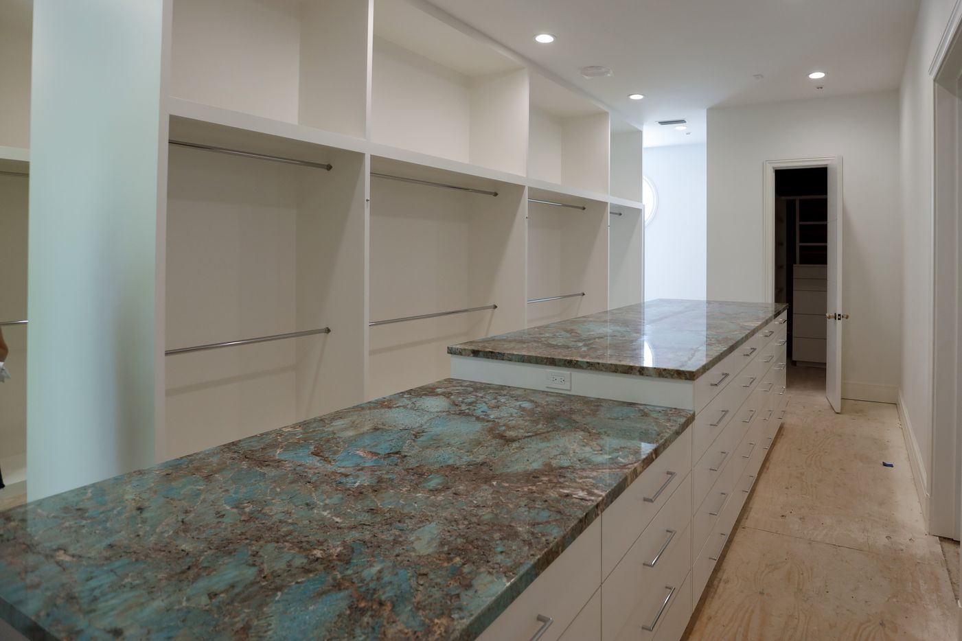 One of two closets in the master bathroom has an Amazonite-topped bank of drawers and three aisles for clothes, shoes and accessory storage.