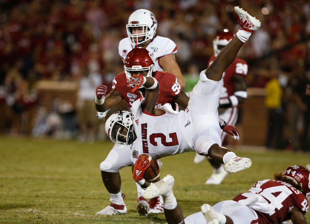 South Dakota running back Kai Henry (2) is tripped up by Oklahoma defensive back Brendan Radley-Hiles (44) in the third quarter of an NCAA college football game Saturday, Sept. 7, 2019, in Norman, Okla. Oklahoma defensive lineman Isaiah Thomas (95) is at rear. (AP Photo/Sue Ogrocki)