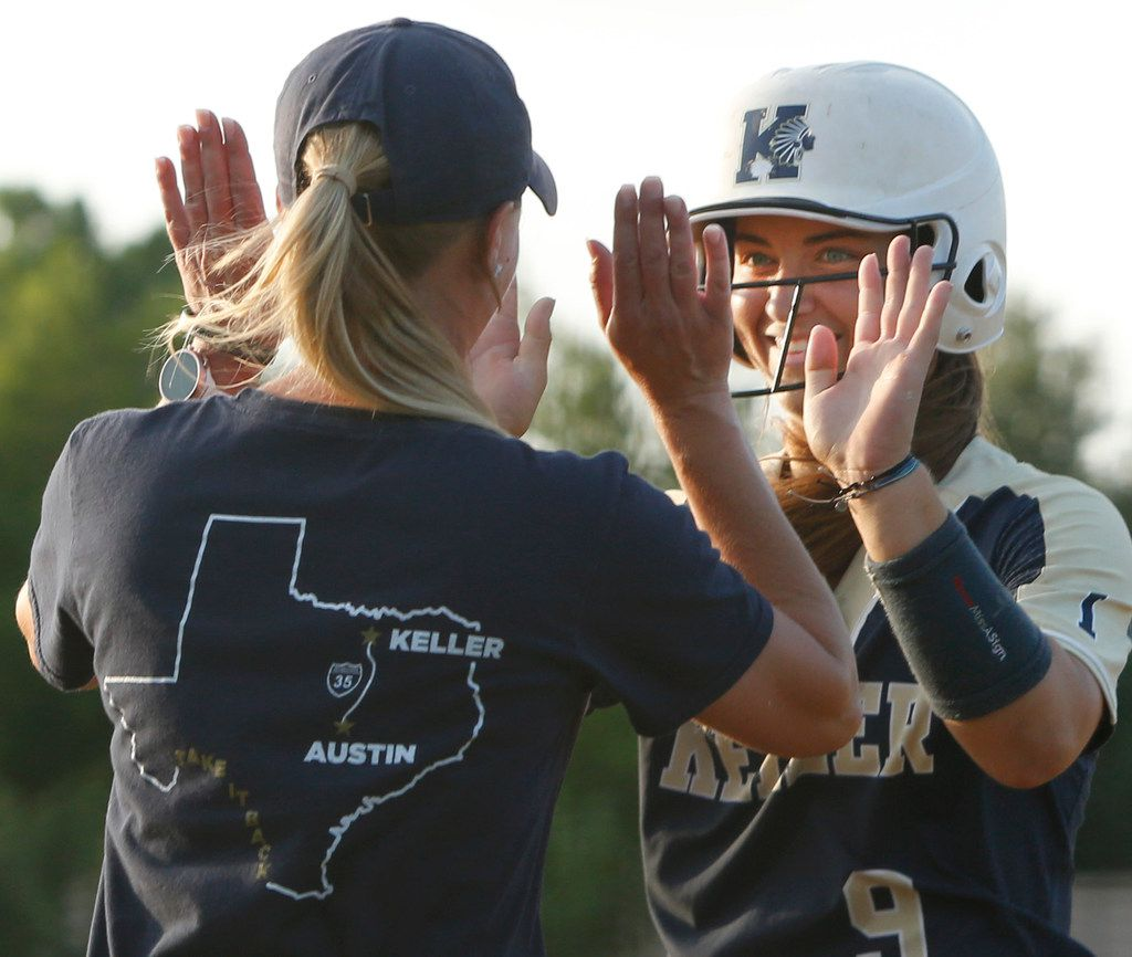 Keller baserunner Alexa Longeliers (9) was all smiles as she receives congratulations from 1st base coach Tiffanie Boone after reaching base during the first inning of play against Northwest Eaton.  The two teams played Game 2 of a best-of-3 Class 6A Region l softball final series at Flower Mound High School in Flower Mound on May 23, 2019. (Steve Hamm/ Special Contributor)