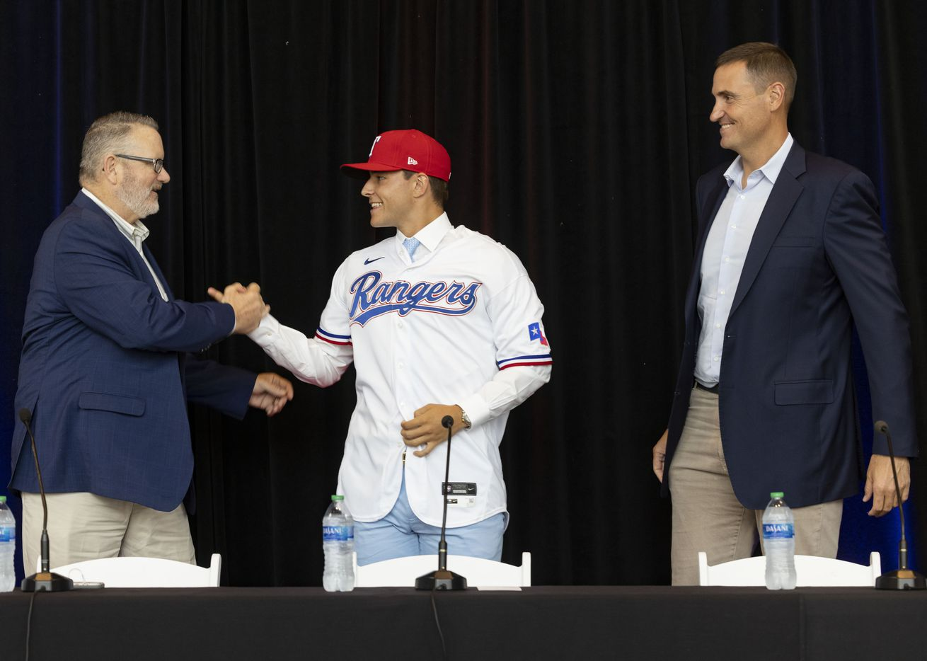 Kip Fagg (left), Texas Rangers Senior Director of Amateur Scouting, Chris Young (right), Rangers Executive Vice President and General Manager, congratulate Jack Leiter from Vanderbilt University after putting on his Texas Rangers jersey following the announcement of his signing on Tuesday, July 27, 2021, at Globe Life Field in Arlington. Leiter was the club's 2021 MLB Draft first round selection and the draft's second overall pick. (Juan Figueroa/The Dallas Morning News)