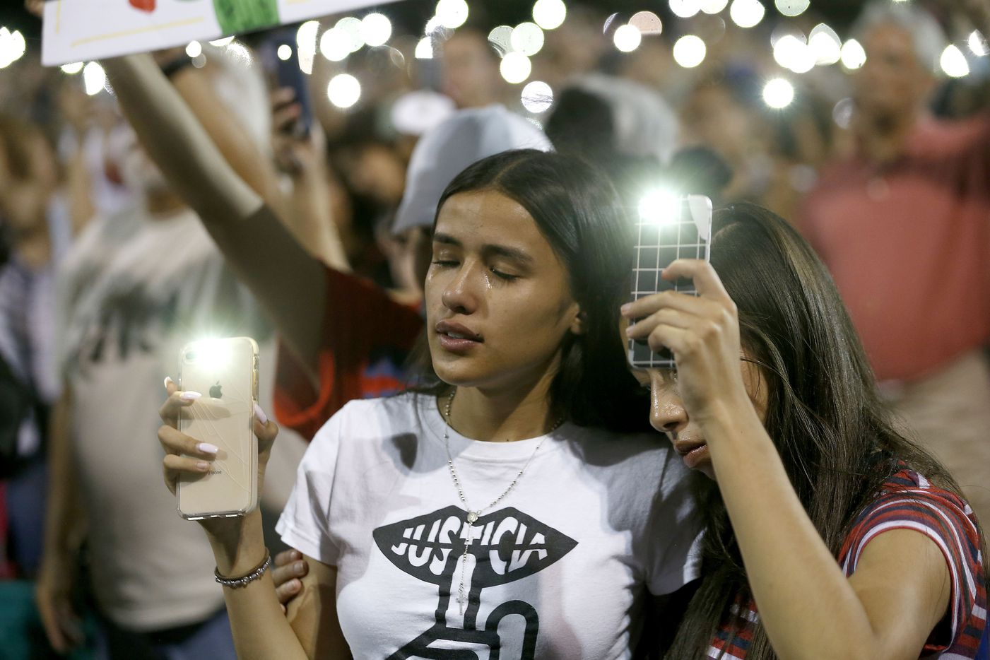 Samantha Salazar (left) and Sarah Estrada join well over a thousand mourners gathered at Ponder Park in El Paso, Texas for a community vigil on Sunday night, Aug. 4, 2019 after a mass shooting at a WalMart the day before left 20 dead and 26 more wounded.
