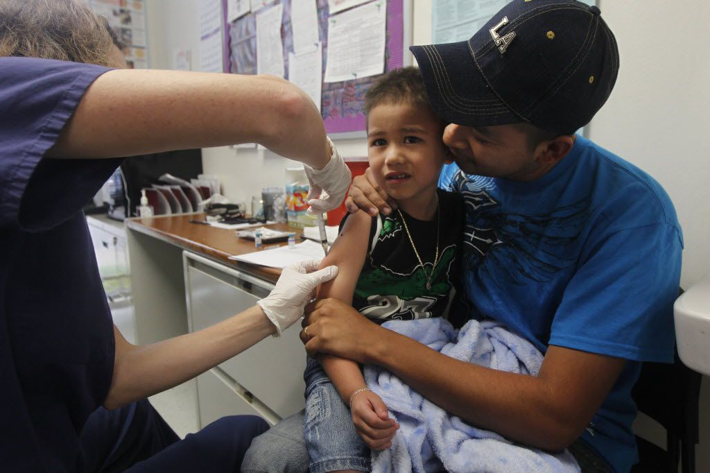 Registered nurse Nicole Kay gives Dilan Lara, 4, one of five immunizations as he is comforted by his father, Gustavo Lara, at the Dallas County Health Department.