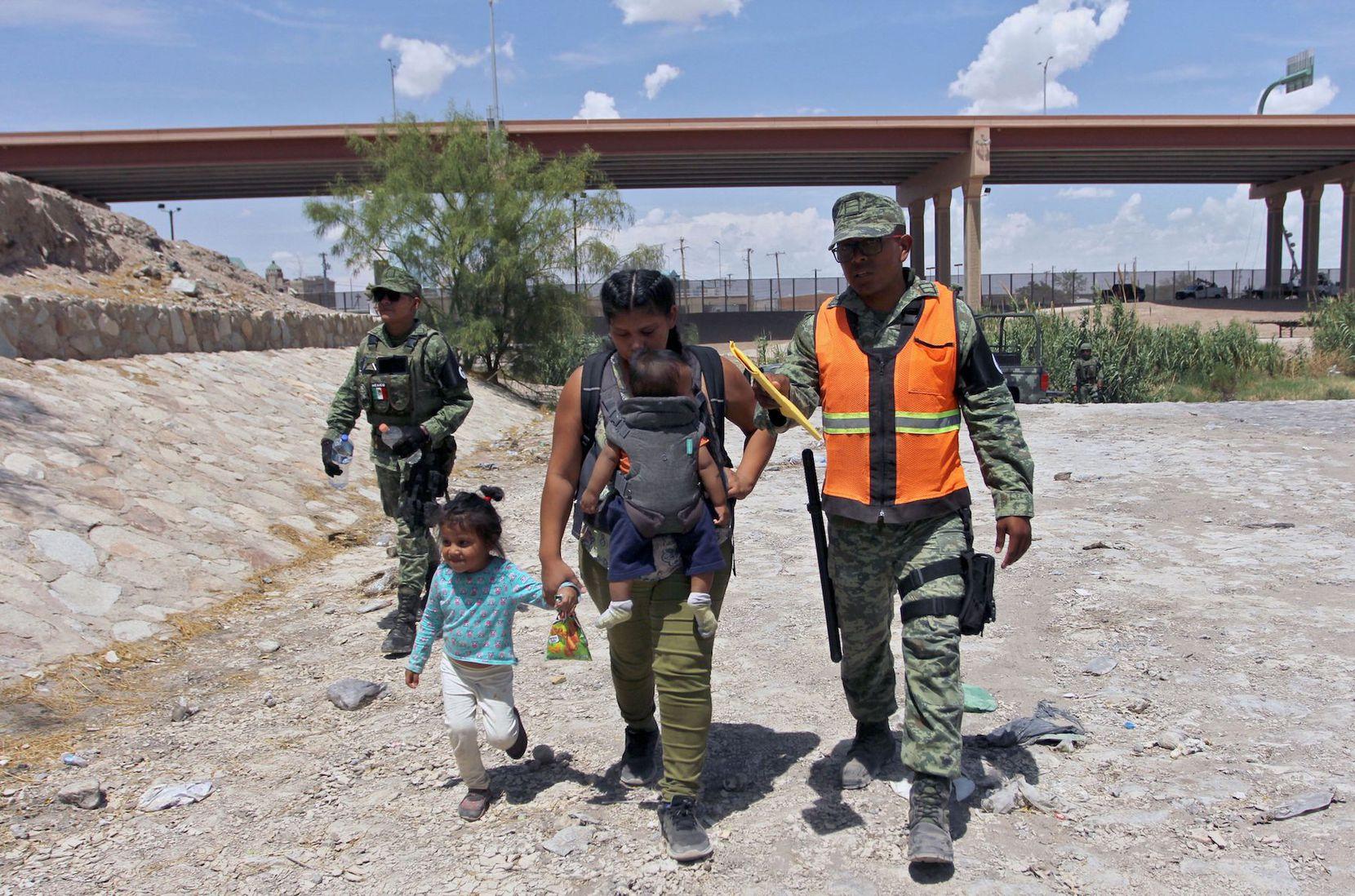 Un elemento de la Guardia Nacional de México acompaña a un mujer con dos niñas en el lado mexicano de la frontera con Estados Unidos. HERIKA MARTINEZ/AFP/Getty Images)