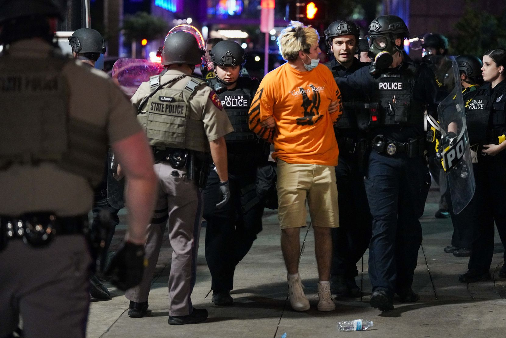 Dallas police arrest a man on Elm Street while working to clear groups of people from downtown streets following a protest against police brutality in the early morning hours of Saturday, May 30, 2020, in Dallas.