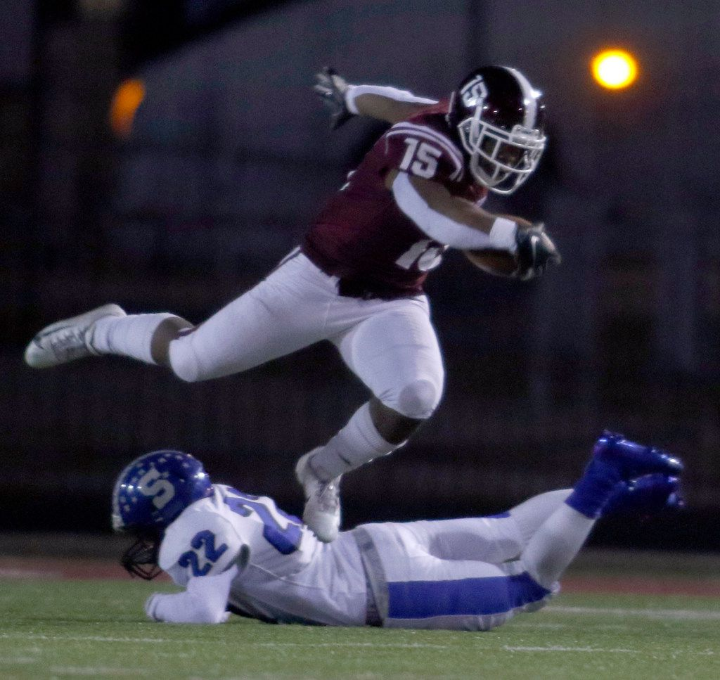 Red Oak running back C.J. Palmer (15) leaps over an attempted tackle by Seagoville defensive back Rickey Smith (22) enroute to a first down carry during first quarter action. The two teams played District 6-5A Division ll football game at Billy Goodloe Stadium in Red Oak on November 7, 2019. (Steve Hamm/ Special Contributor)