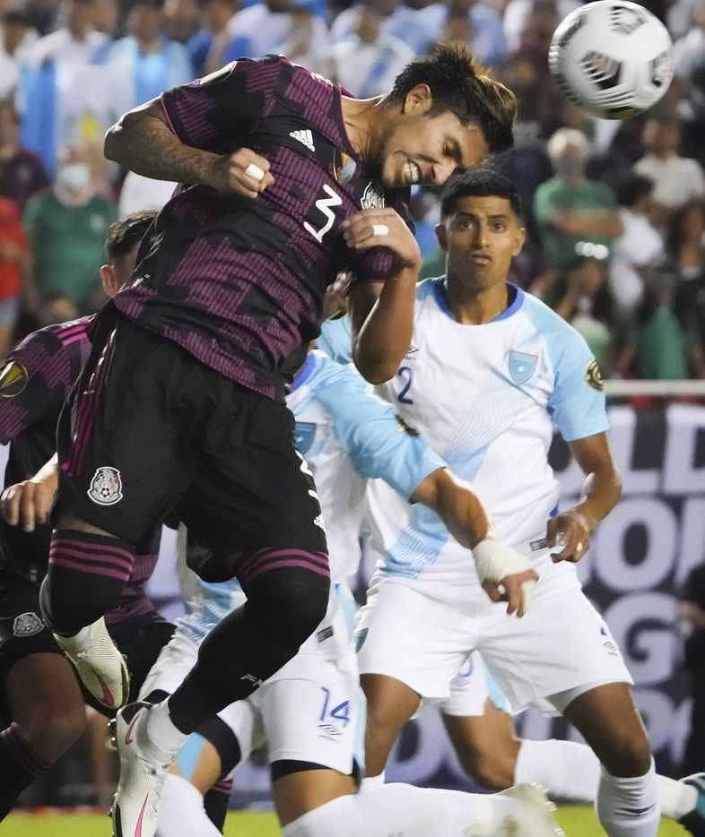 Mexico defender Carlos Salcedo (3) wins a header in front of Guatemala forward Darwin Lom (14) and defender Moisés Hernández (2) during the first half of a CONCACAF Gold Cup Group A soccer match at the Cotton Bowl on Wednesday, July 14, 2021, in Dallas.