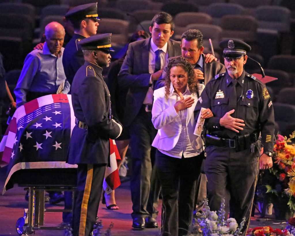The family of slain Dallas Officer Rogelio Santander walks past his flag-draped casket during his funeral at Lake Pointe Church in Rockwall.