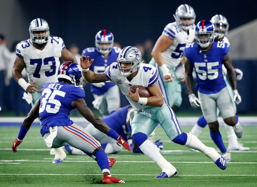 Dallas Cowboys quarterback Dak Prescott (4) take off running with the ball on a keeper against New York Giants cornerback Curtis Riley (35) during the first quarter at AT&T Stadium in Arlington, Texas, Sunday, September 16, 2018. (Tom Fox/The Dallas Morning News)