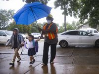 (From right) Pre-K teacher's assistant Felicia Hay escorts an excited Natalia Bautista, 5, and Jaden Ortega,8, into the first day of school on Monday, Aug. 2, 2021, at H.I. Holland Elementary School in Dallas. (Juan Figueroa/The Dallas Morning News)