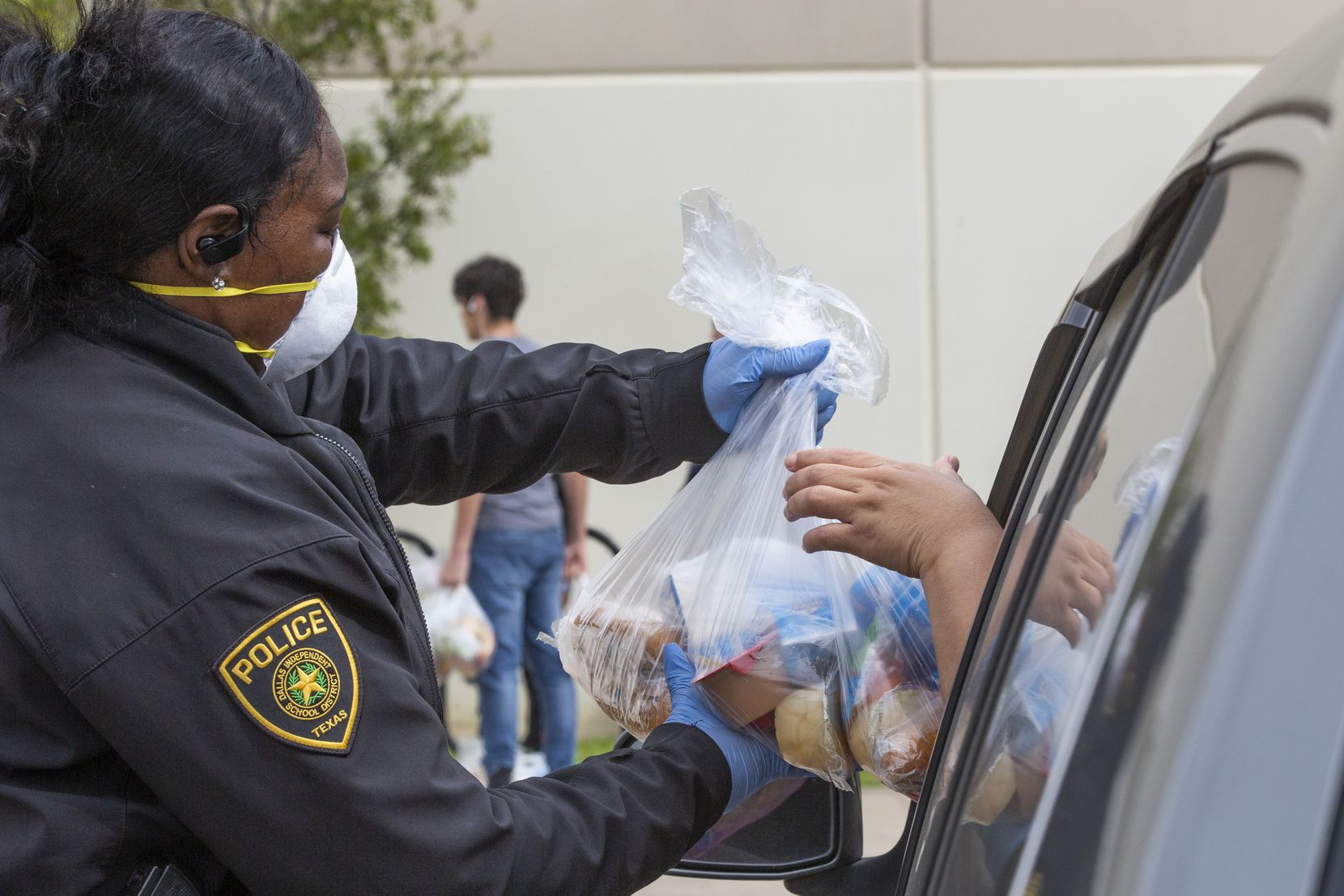 Dallas police Officer Sherneka Coleman distributed meals at Medrano Middle School in Dallas on Thursday.
