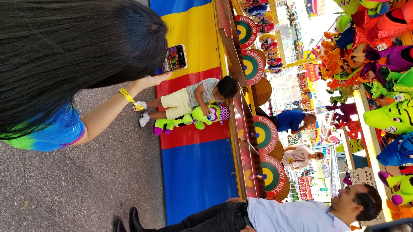 Cristián Castro, 4, won a plush neon green duck by rolling four balls each into a different color target. Proud dad Julián Castro is at right as his mom, Erica Castro, takes a photo of the trophy.