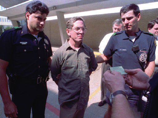 Dallas police read George Douglas Lott, center, his rights after he turned himself in to the Dallas police in 1992.  Lott, 45, said he attacked courthouse workers to draw attention to his son and his four-year-old divorce case.