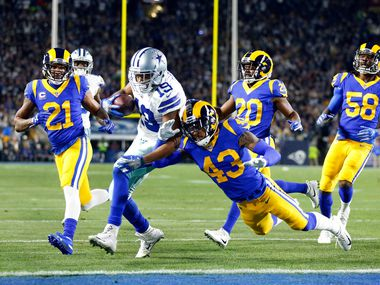 FILE - Cowboys receiver Amari Cooper (19) scores a touchdown as he bounces off Rams safety John Johnson (43) during the first quarter of an NFC divisional-round playoff game at LA.. Memorial Coliseum in Los Angeles on Saturday, Jan. 12, 2019.