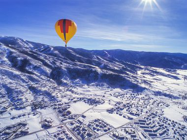 A hot-air balloon drifts high above Steamboat Springs, Colo..  In addition to skiing, visitors can enjoy winter horseback and sleigh rides, hot-springs soaks and classes in winter driving.
