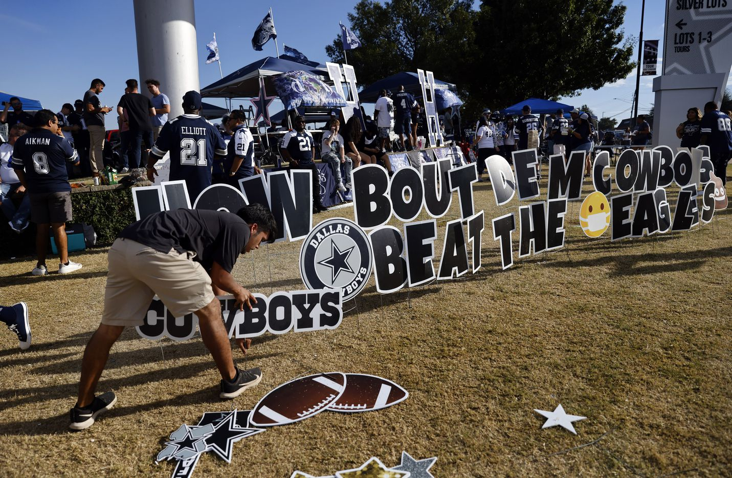 Dallas Cowboys fan Alex Perez of Dallas constructs a game day 'yard sign' display outside of AT&T Stadium in Arlington, Monday, September 27, 2021. He says he puts one up for every home opener. This one reads, How Bout Dem Cowboys, Beat The Eagles'. (Tom Fox/The Dallas Morning News)