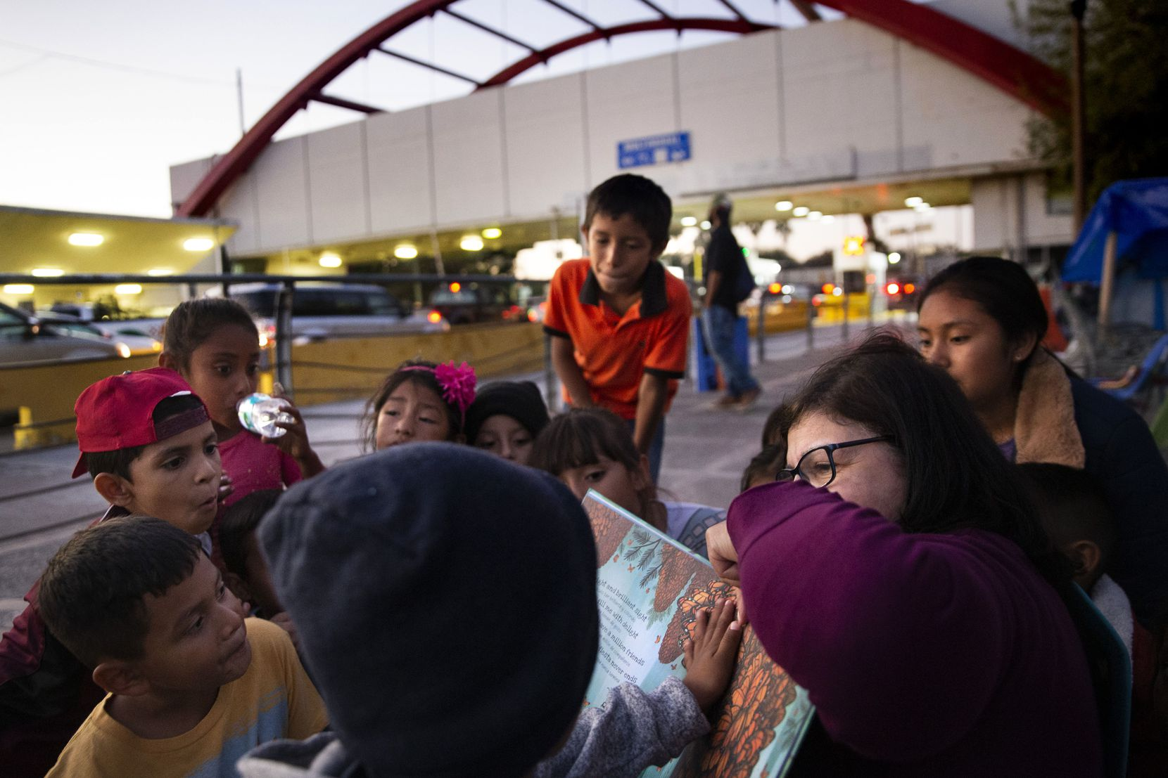 A Houston volunteer (right) reads to a group of asylum-seeking children by the Gateway International Bridge in Matamoros, Mexico, on Dec. 14, 2019.