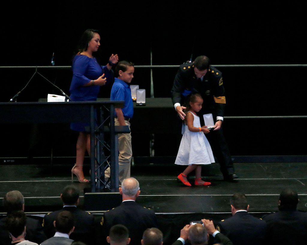 Lyncoln Zamarripa, daughter of slain officer Patrick Zamarripa, receives the Police Cross from Interim Police Chief David Pughes as Kristy Zamarripa and her son Dylan Hoover look on.