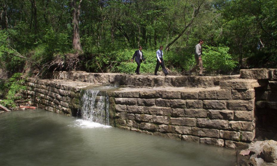 From left: Warren Johnson, president of the Allen Heritage Guild; Don Horton, director of parks for the city of Allen; and Jim Waldbauer, chairman of the Allen Parks Board, cross an old dam on Cottonwood Creek.