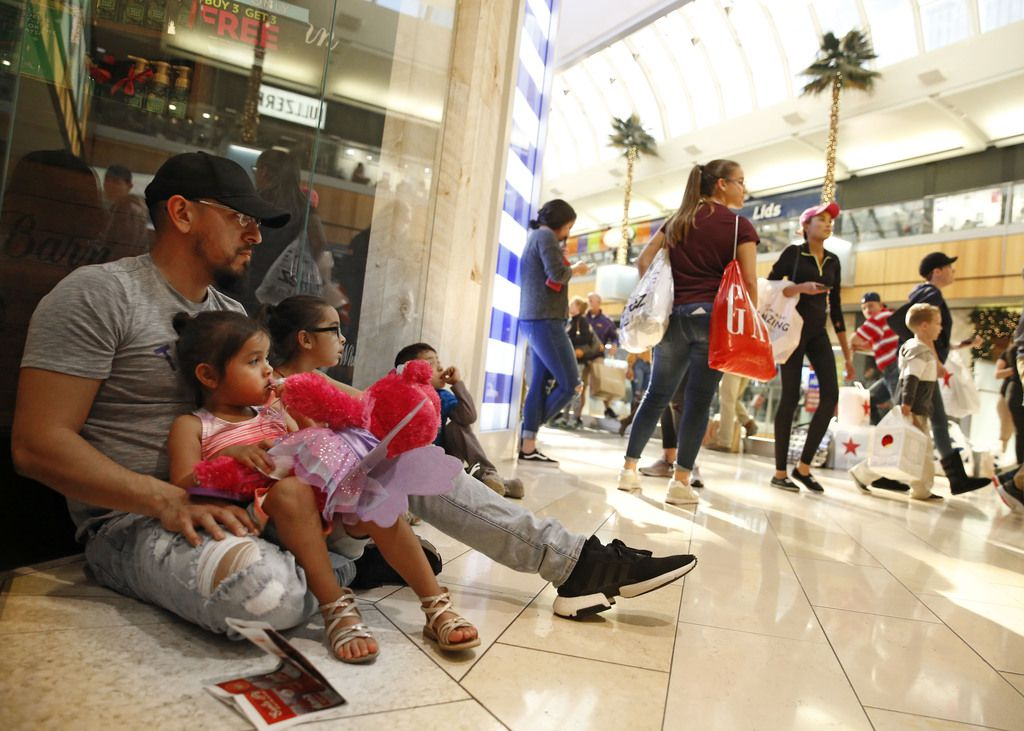 Holiday shoppers during Thanksgiving weekend last year at Galleria Dallas. Ramiro Rodriguez (from left) with his family Mallory, 3, Alena, 6, and Elijah, 5, waited outside a store.