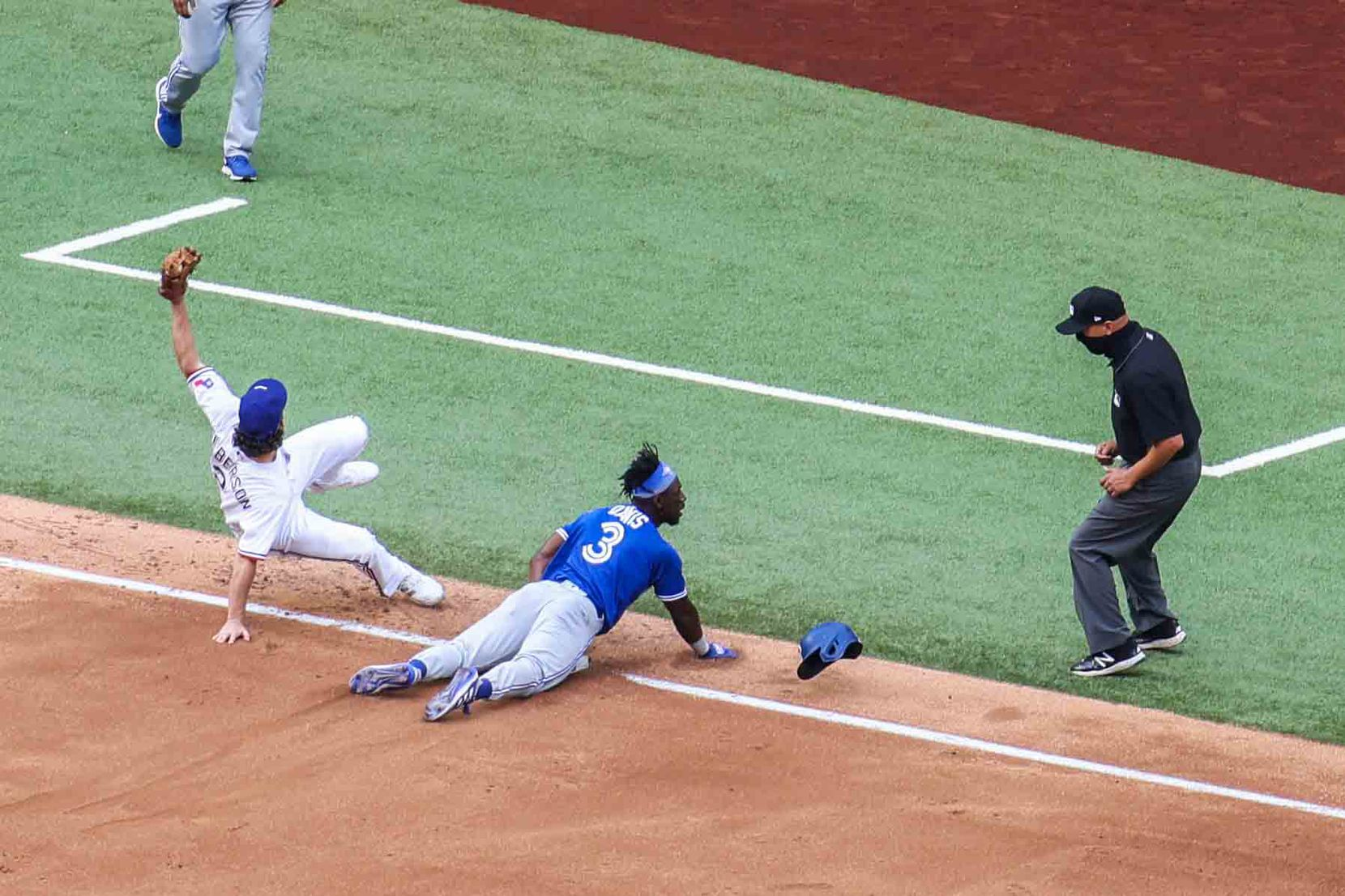 Toronto Blue Jays outfielder Jonathan Davis No. 3 gets tagged out by Texas Ranger infielder Charlie Culberson No. 2 as Davis tries to steal third base at the Globe Life Field during opening day in Arlington, Texas on Monday, April 5, 2021. (Lola Gomez/The Dallas Morning News)