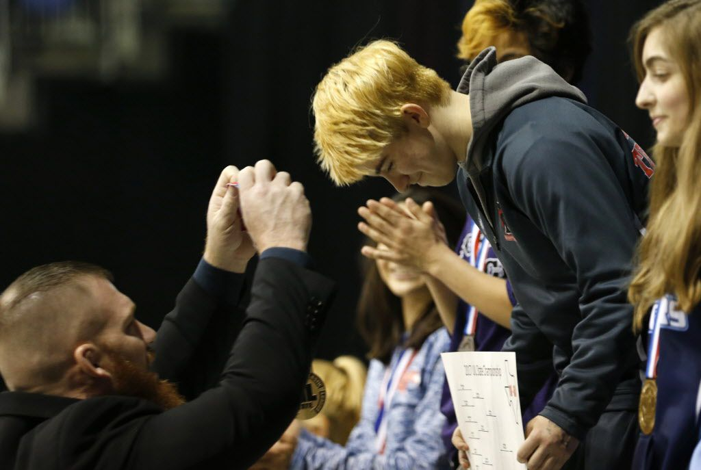 Euless Trinity's Mack Beggs receives his first place medal from Trinity head coach Travis Clark after defeating Katy Morton Ranch's Chelsea Sanchez in the championship match of the 6A girls 110 weight class during the UIL Wrestling State Tournament at Berry Center in Cypress on Saturday, February 25, 2017. Beggs defeated Sanchez to win the championship. (Vernon Bryant/The Dallas Morning News)