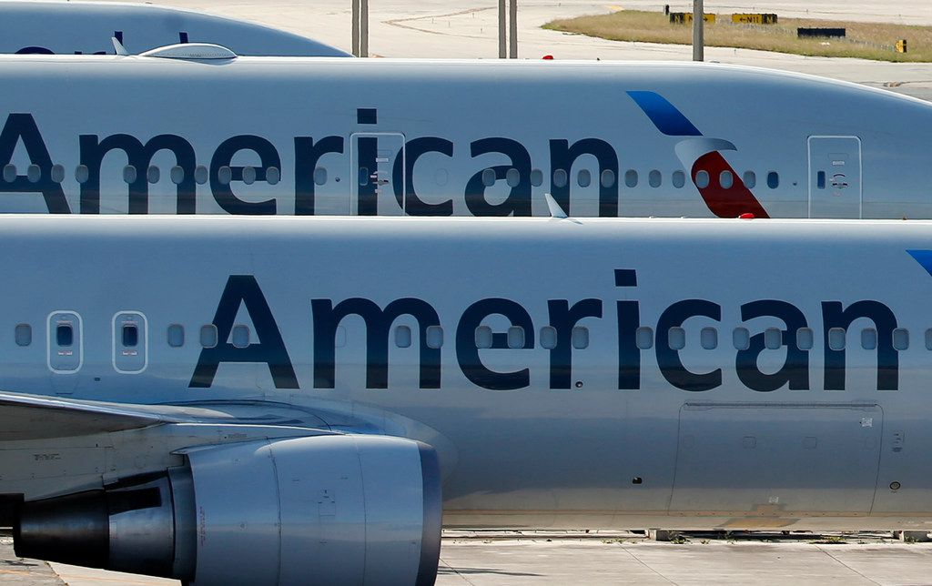 FILE - In this Monday, Nov. 6, 2017, file photo, a pair of American Airlines jets are parked on the airport apron at Miami International Airport in Miami. Dozens of companies have announced they are giving their employees bonuses, following the passage of the Republican tax plan that President Donald Trump signed into law in December. American Airlines is handing out $1,000 bonuses to its employees. (AP Photo/Wilfredo Lee, File)