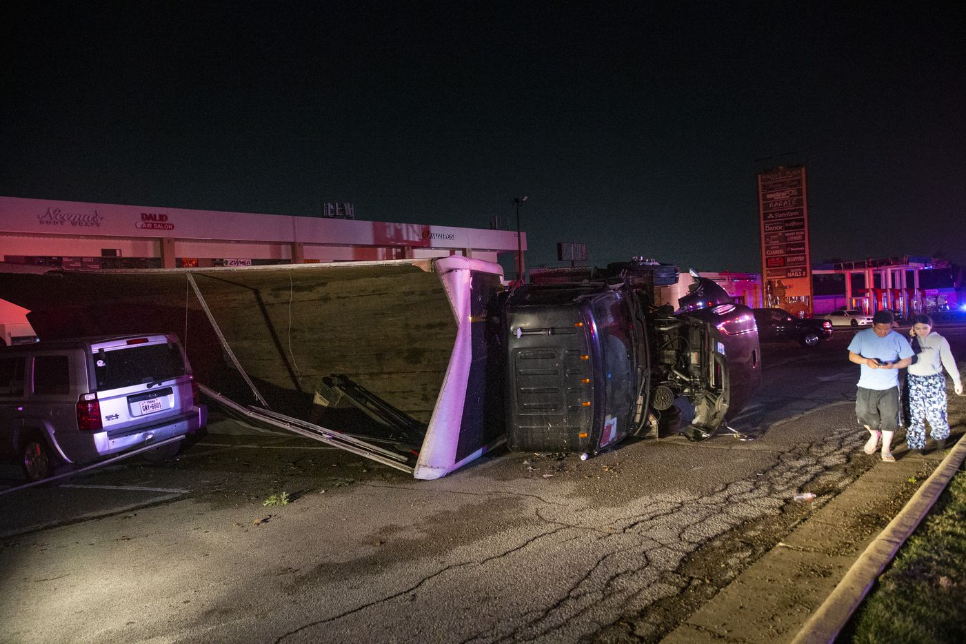 People walk past an overturned semi-truck at a shopping center on the corner of Walnut Hill Lane and Marsh Lane after a tornado hit parts of northern Dallas on Sunday, Oct. 20, 2019.