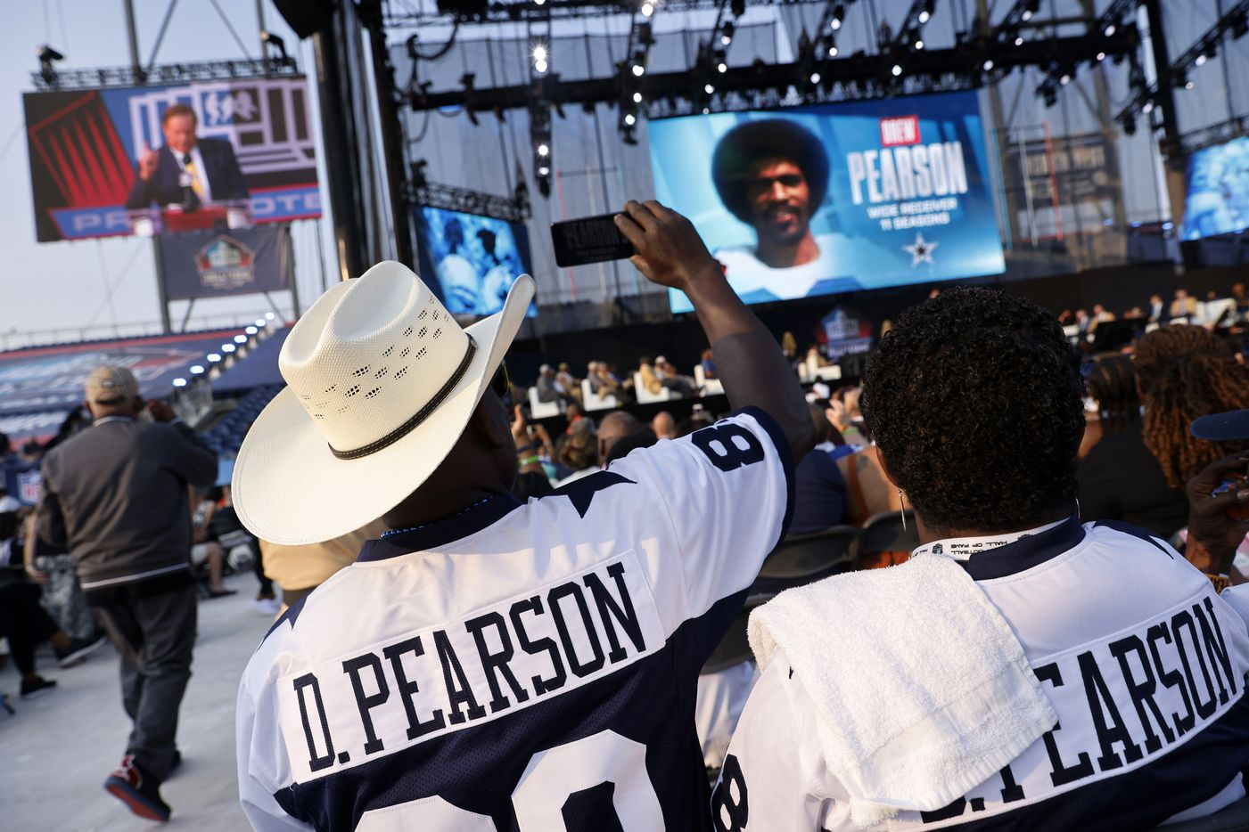 Mike Fisher takes a photo as Pro Football Hall of Fame inductee Drew Pearson of the Dallas Cowboys is introduced during the Class of 2021 enshrinement ceremony at Tom Benson Hall of Fame Stadium in Canton, Ohio, Sunday, August 8, 2021. (Tom Fox/The Dallas Morning News)