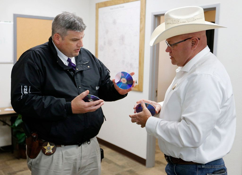 Wise County sheriff investigator Luke Campbell hands over DVD copies of evidence to special ranger John Bradshaw of the Texas and Southwestern Cattle Raisers Association.