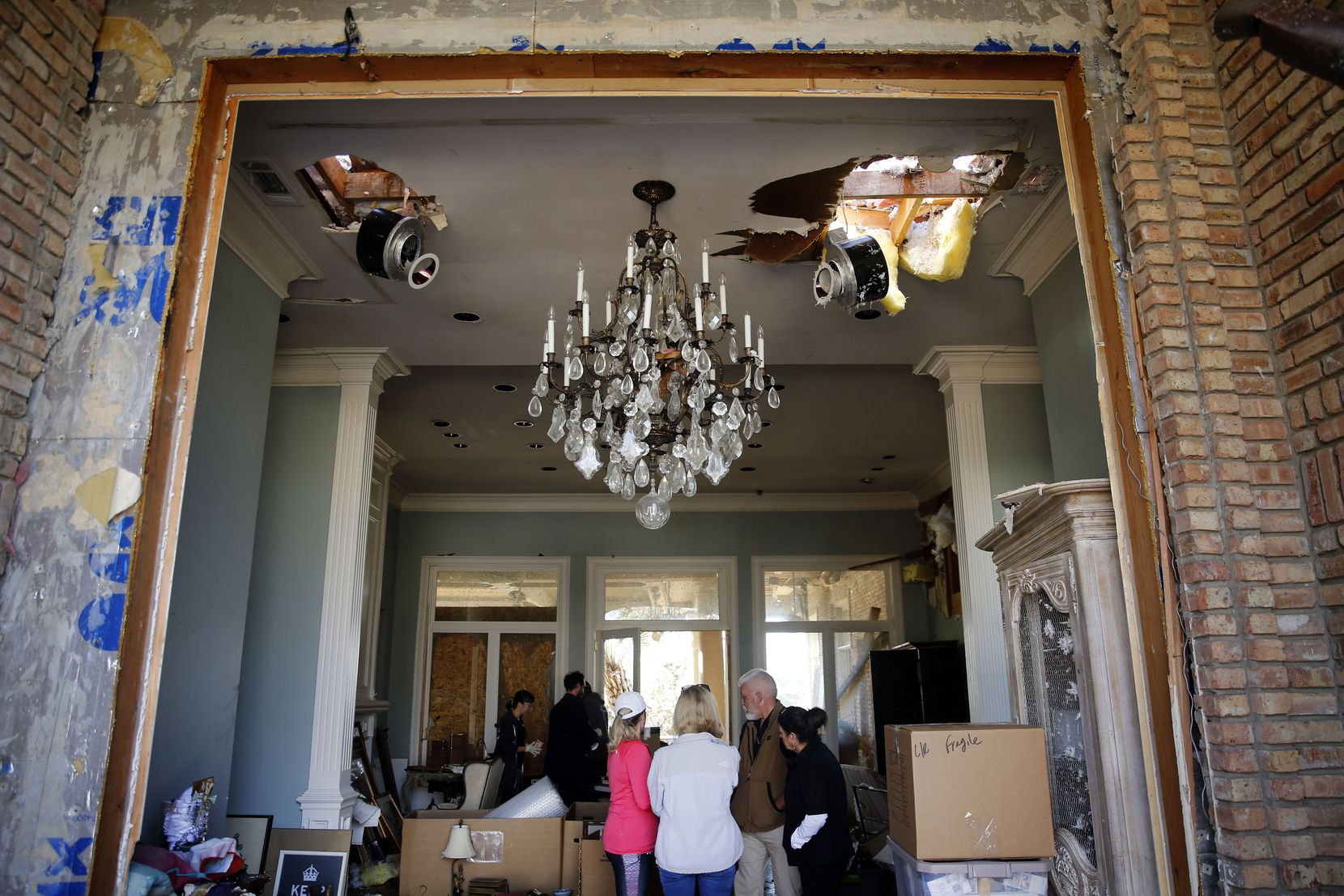 Homeowner Brenda Schneider said the crystal chandelier in her front entryway on Palomar Lane wasn't damaged, despite the front door being blown out. She and her wheelchair-bound husband, Fred, escaped through a broken-out dining room window, Tuesday, Oct. 22, 2019. Art of Dallas-Fort Worth helped remove artwork from their home.