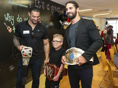 "Patient Jacob Mowl (Patient, 15 y/o) takes a photo wearing one of the WWE Champions belts with Roman Reigns (black polo) and Seth Rollins (wearing jacket).  WWE brought some of their wrestlicng personalities for an energetic event in the CHST Dallas Butterfly Atrium where five patients had the chance to be costumed ""Superstars"" and be introduced to a cheering crowd."