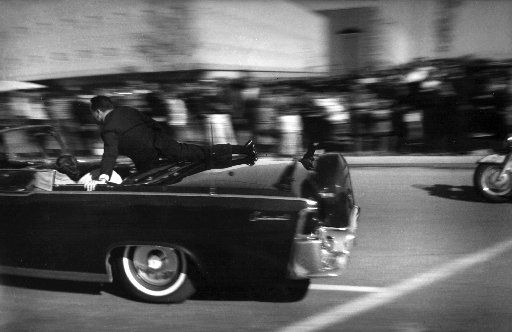Pres. John F. Kennedy's limo speeds toward Parkland Hospital moments after he was shot in Dallas, with Secret Service Agent Clinton Hill jumping into the back seat, on Nov. 22, 1963 in Dallas.