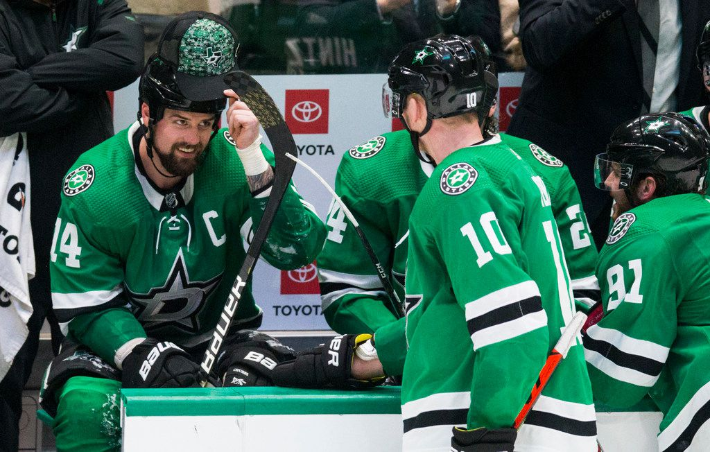 Dallas Stars left wing Jamie Benn (14) puts on a hat thrown on the ice by a fan after he scored a goal for a hat trick during the third period of an NHL game between the Dallas Stars and the Carolina Hurricanes on Tuesday, February 11, 2020 at American Airlines Center in Dallas.