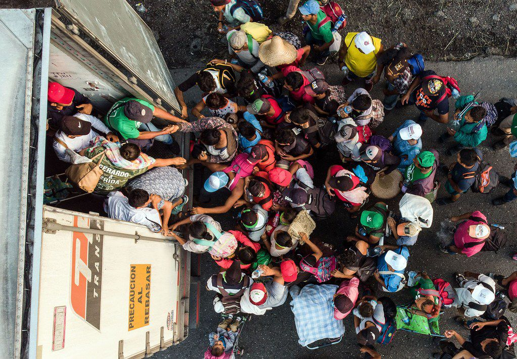 Honduran migrants taking part in a caravan heading to the U.S. get on a truck near Pijijiapan, southern Mexico on October 26, 2018.