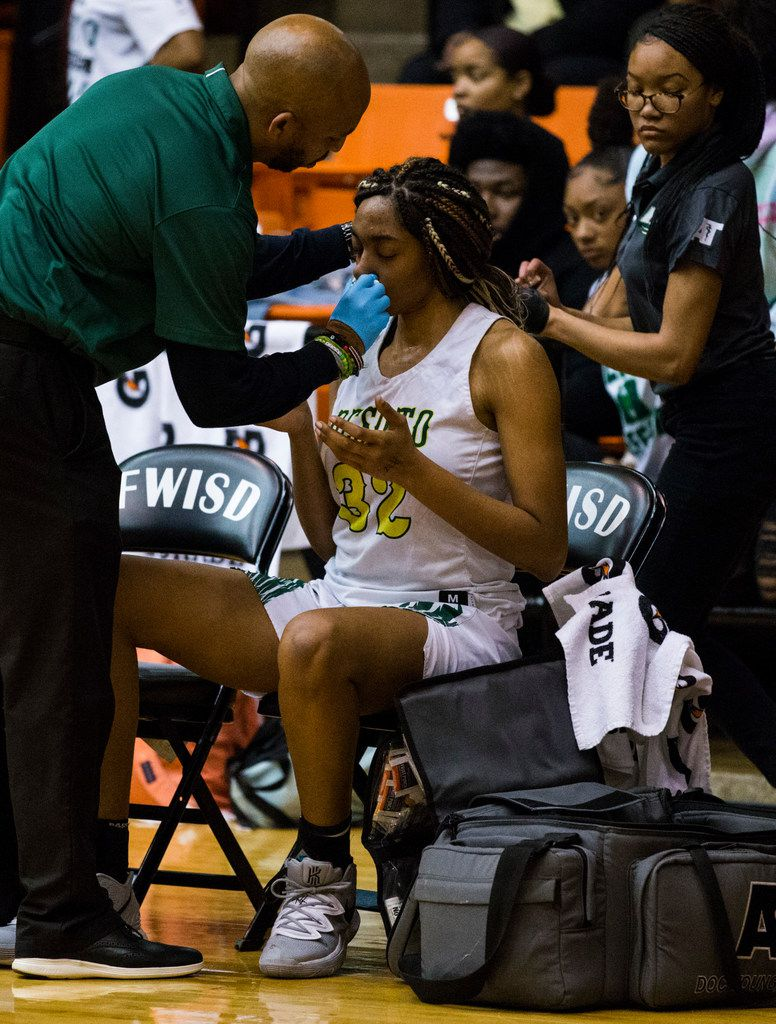 DeSoto's Tina Herron (32) is treated after an injury during the third quarter of a Class 6A Region I quarterfinal girls basketball game between Duncanville and DeSoto on Tuesday, February 25, 2020 at Wilkerson-Greines Activity Center in Fort Worth. (Ashley Landis/The Dallas Morning News)