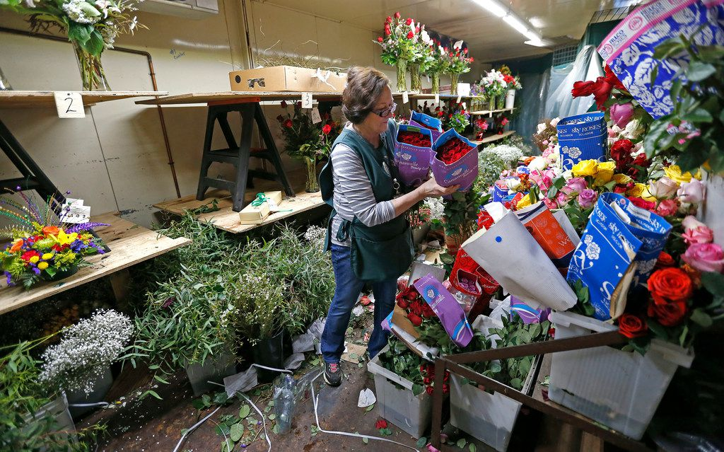 Designer Teresa Bain picked up roses inside a cooler at McShan Florist in Dallas on Feb. 12, 2018.
