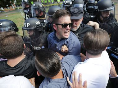 """Richard Spencer (center) and his supporters clash with Virginia State Police in Emancipation Park after the """"Unite the Right"""" rally was declared an unlawful gathering Aug. 12, 2017, in Charlottesville, Va."""