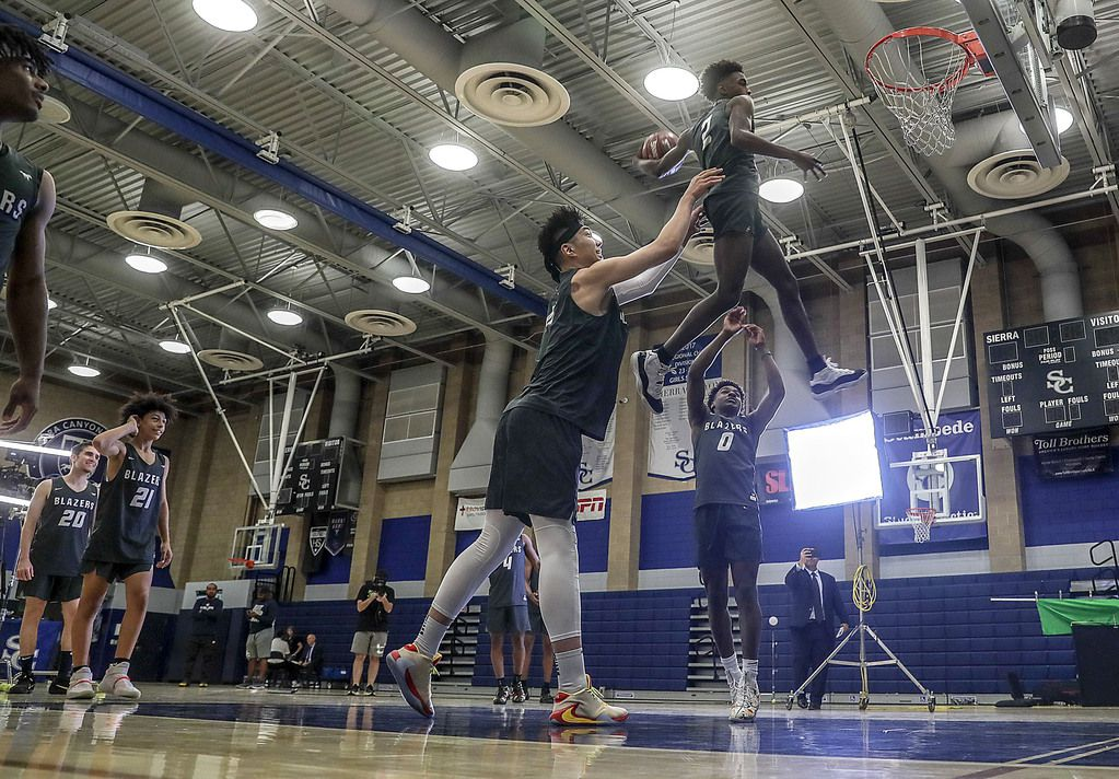 PORTER RANCH, CA, THURSDAY, OCTOBER 10, 2019 - Sierra Canyon players Harold Yu, left, and Bronny James, background (0) lift Zaire Wade to a slam dunk during basketball media day. (Robert Gauthier/Los Angeles Times)