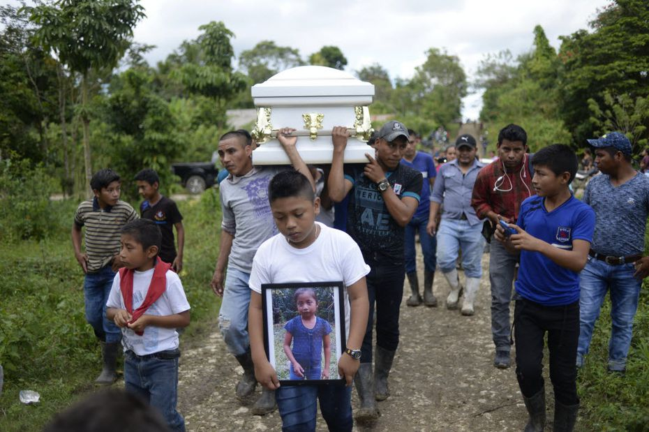 A boy carries a picture of Guatemalan seven-year-old Jakelin Caal, who died in a Texas hospital two days after being taken into custody by US border patrol agents in a remote stretch of the New Mexico desert, as her coffin is taken from Raxruha to the cemetery in San Antonio Secortez, both villages in Alta Verapaz Department, 320 km north of Guatemala City, on December 25, 2018.