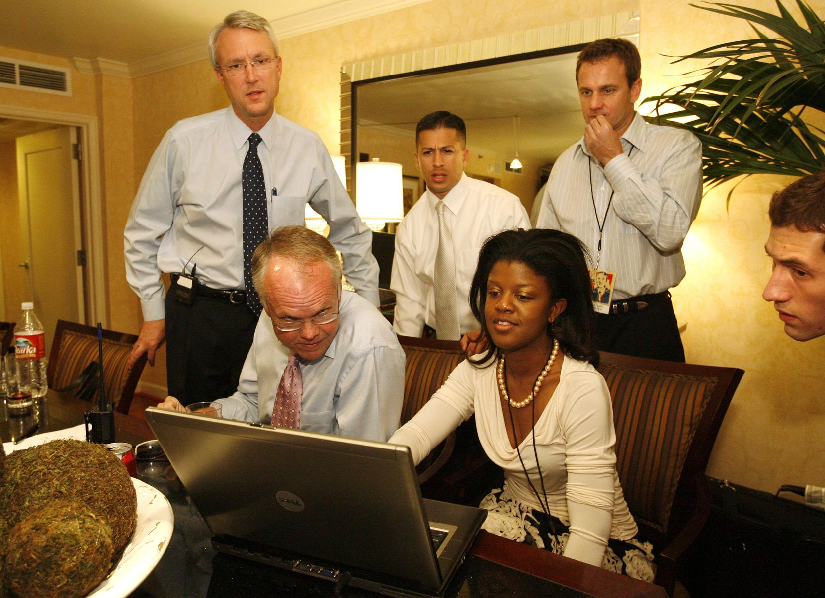 Democratic gubernatorial candidate Chris Bell (left), Fred Ellis (sitting left), finance director, Rowland Garza (standing center with tie) travel aide, Chris Hughes (standing center right) campaign chairman, Trista Allen (sitting center) political director, and Adam Briscoe (far right) travel aide look over the results at the Intercontinental Hotel in Houston on Tuesday, November 7, 2006.