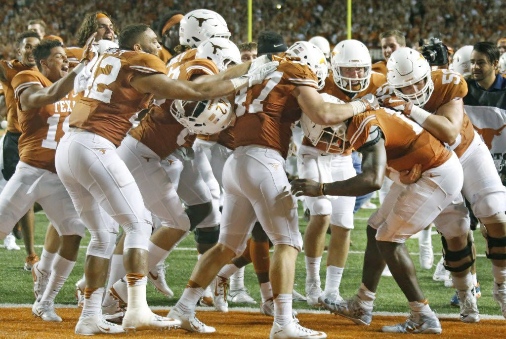 Teammates mob Texas quarterback Tyrone Swoopes after he scored the winning touchdown in the second overtime during the Notre Dame Fighting Irish vs. the University of Texas Longhorns NCAA football game at Darrell K. Royal Memorial Stadium in Austin on Sunday, September 4, 2016. (Louis DeLuca/The Dallas Morning News)