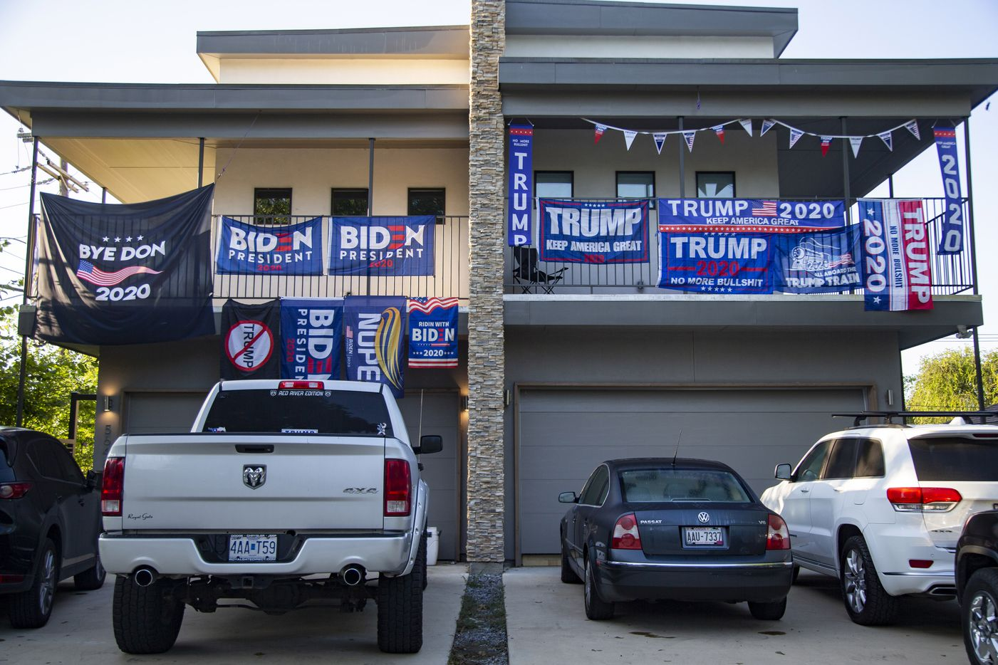 Neighbors in a two-story apartment have competing Biden and Trump banners draped over their balconies at the corner of Anita St and Greenville Ave in Dallas Friday, Sept. 25, 2020.