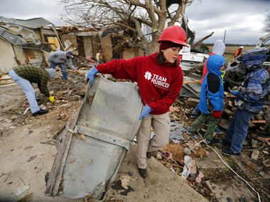 Team Rubicon volunteer Molly Gayden of Fort Worth hauls a piece of garage door to the curb as they clean up the tornado ravaged home on Mesa Wood Drive in Glenn Heights.