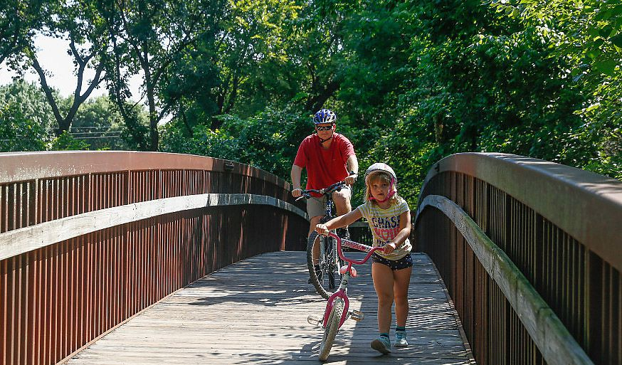 Zoe Voelker, 6, and her dad, Al Voelker, cross one of the wooden bridges into Parr Park in Grapevine. The city offered more than $1 million in incentives to lure The Trade Group from Carrollton.