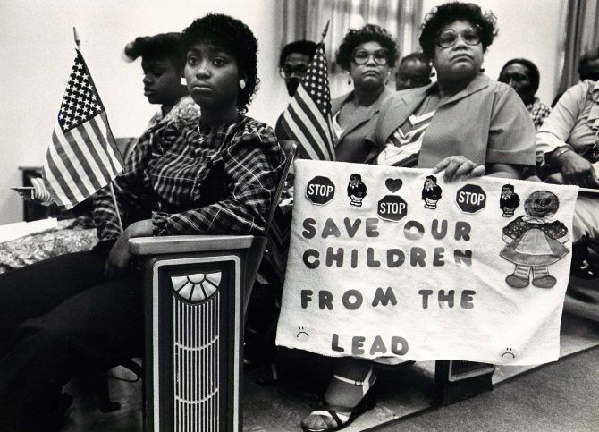 Ina Bell Daniels McGee (center, holding flag) and sister Nina Nell Daniels Webster at a 1983 meeting of a task force about a West Dallas lead smelter. The twins were involved in many causes over the years.