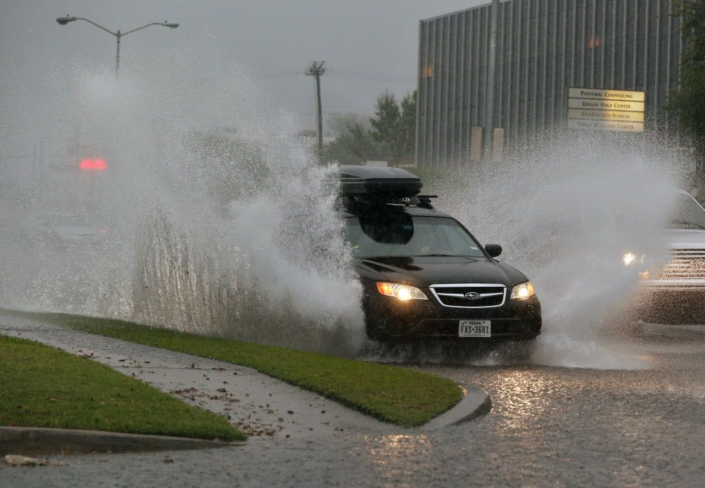 Cars plowed through flooded roads on Lemmon Avenue during torrential rains in Dallas. (Nathan Hunsinger/Staff Photographer)