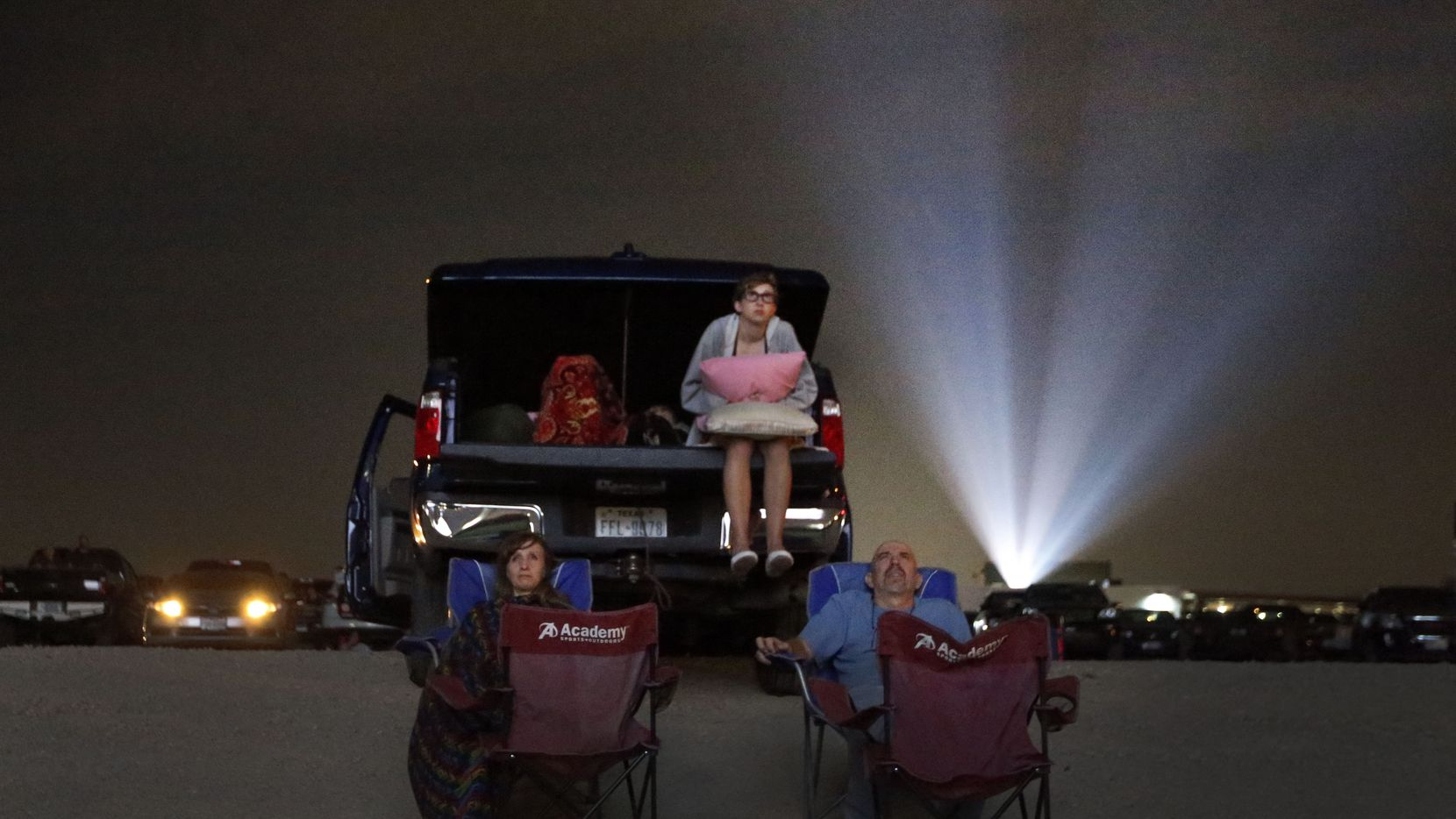 People watch a drive-in movie.