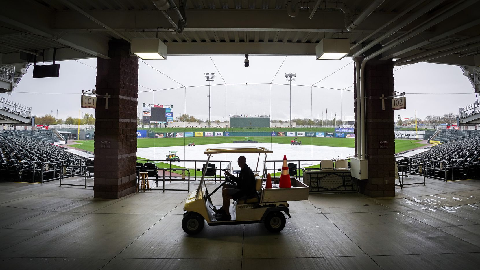 A stadium worker drives a cart through Surprise Stadium as tarp covers the field while rain falls on Saturday, Feb. 22, 2020, in Surprise, Ariz.