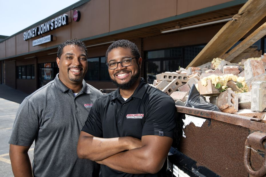 Juan and Brent Reaves, left to right, are the brothers and co-owners of a barbecue joint in Dallas called Smokey John's. Here, in 2018, they stand next to a pile of rubble at their Mockingbird Lane restaurant, which was closed for more than a year following a fire.