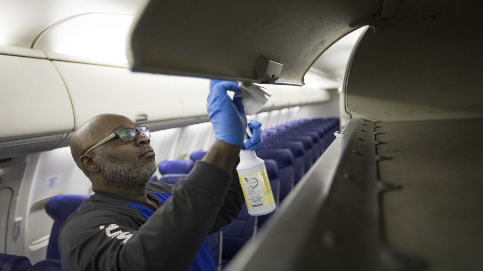 A Southwest Airlines employee cleans a plane as the airline steps up hygiene measures to protect passengers and crew members from COVID-19.